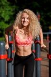 Sporten van het foto trekt de krullende blonde op sportensimulator uit in park Stock Afbeelding