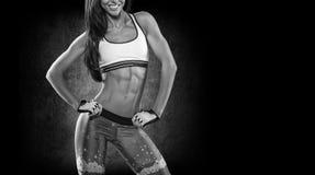 sporten Vrouw bij de gymnastiek die het uitrekkende oefeningen en glimlachen doen stock afbeeldingen