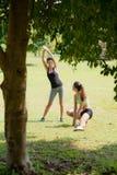 Sporten, vrouwelijke vrienden die na het aanstoten ontspannen Stock Afbeeldingen