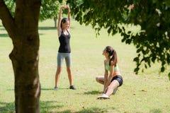 Sporten, vrouwelijke vrienden die na het aanstoten ontspannen Royalty-vrije Stock Fotografie
