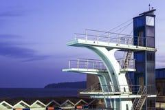 Sportenduikplank door krachtige zoeklichten op de openluchtpool op een donkere achtergrond die van de nachthemel wordt aangestoke royalty-vrije stock afbeelding