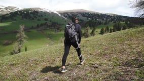Sportenmeisje met een rugzak in een het lopen gang langs de groene bergweiden In de bergen stock video