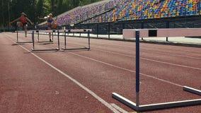 Sportenmeisjes die gemakkelijk barrières op renbaan, selectie voor de concurrentie overbruggen stock video