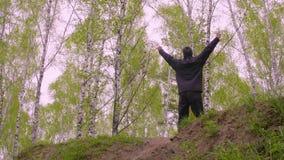 Sportenmens die op heuvel lopen en handen omhoog op de achtergrond van berkbomen opheffen stock video