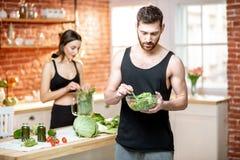 Sportenpaar die gezond vegetarisch voedsel op de keuken eten stock fotografie