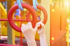 sportenringen voor kinderen in de openbare speelplaats, met kid& x27; s hand, zonlichteffect royalty-vrije stock afbeeldingen