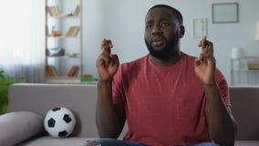 Sportenverdediger die vingers kruisen die op spel op TV letten, die nationaal team toejuichen