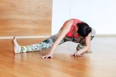 Sportenvrouw die het uitrekken in de zaal doen zich vóór yoga Royalty-vrije Stock Foto