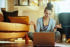 Sportenvrouw het letten op yogaleerprogramma op Internet via laptop stock fotografie