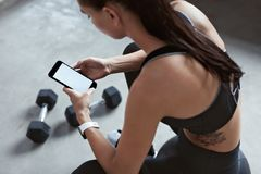 Sportenvrouw in Maniersportkleding die Telefoon bij de Opleiding met behulp van stock foto