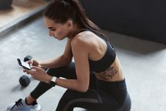 Sportenvrouw in Maniersportkleding die Telefoon bij de Opleiding met behulp van stock foto's