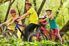 Sportfamilj som har gyckel som cyklar i skogen fotografering för bildbyråer