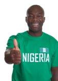 Sportfan von Nigeria, das sich Daumen zeigt lizenzfreie stockbilder