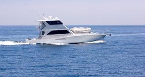 Sportfisher Yacht at Sea. Starboard profile view of white sportfisher yacht underway Stock Photo