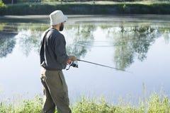 Sportfiskaren i en hatt och gummistöveler står över vattnet med en metspö Royaltyfri Fotografi