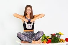 Sportfitness vrouw, fitness vrouwenbeenkappen, Jong mooi meisje met lang bruin haar in een sportenbovenkant en legging met vrucht stock fotografie