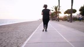 Sportflicka i svart köra för dräkt som är utomhus- arkivfilmer
