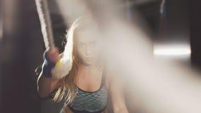 Sportflicka som utarbetar med rep i den mörka idrottshallen långsamt lager videofilmer