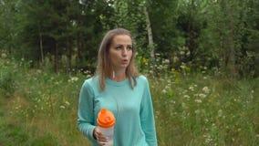 Sportflickadricksvatten från flaskan, når att ha joggat Arkivbilder