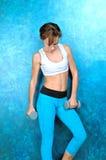 Sportflickan i kläder för kondition står nära den blåa väggen Royaltyfria Foton