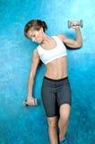 Sportflickan i kläder för kondition står nära den blåa väggen royaltyfri fotografi