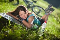 Sportflickan lägger på ett gräs med en översikt nära cykeln Arkivfoton