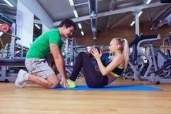 Sportflickan som gör abs, övar med en instruktörman på golvet a Arkivbild