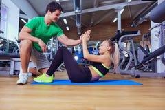Sportflickan som gör abs, övar med en instruktörman på golvet a Arkivbilder