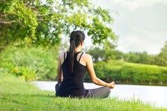Sportflickan som mediterar i naturgräsplan, parkerar på soluppgången Arkivfoto