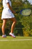 Sportflickan står med racket på domstolen på den soliga sommardagen Royaltyfria Bilder
