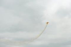 Sportflygplanet utför konstflygningdiagram i himlen Arkivbild