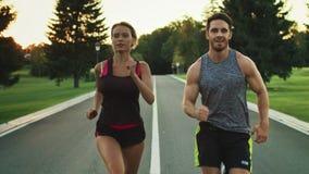 Sportfolket som kör i, parkerar tillsammans Unga par som joggar på den utomhus- genomköraren lager videofilmer