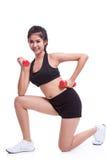 Sportfrau, die Übung mit anhebenden Gewichten tut Stockbild