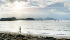 Sportfrau, die auf dem Strand läuft Lizenzfreie Stockfotos