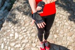 Sportfrau, die auf Handschuhe sich setzt Stockfotografie