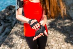 Sportfrau, die auf Handschuhe sich setzt Lizenzfreie Stockbilder