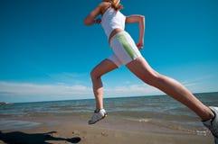 Sportfrau, die auf Strand läuft Stockfotos