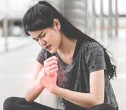 Sportfrau, die eine Verletzung auf ihrer Handgelenkhand hat stockbilder