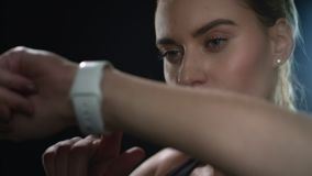 Sportfrau, die an Hand intelligente Uhr im schwarzen Studio verwendet Portr?t der Eignungsfrau stock video footage