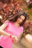 Sportfrau, die ihre Uhr überprüft Stockbild
