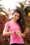 Sportfrau, die ihre Uhr überprüft Stockfoto