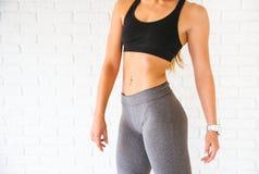 Sportfrau, die im photostudio über Backsteinmauer aufwirft Eignungsmotivation Lizenzfreies Stockbild