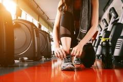 Sportfrau, die Turnschuhseil bindet Sportzentrum und Eignungsturnhalle Co Stockfoto