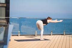 Sportfrau, die Yogaübung auf Hoteldach mit Bretterbodenstand auf Yogamatte ausdehnend tut Lizenzfreie Stockbilder