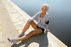 Sportfrau entspannen sich auf sitzendem Wasser des Piers Lizenzfreie Stockbilder