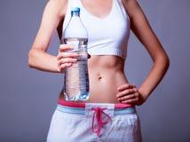 Sportfrau mit Flasche. Stockbild