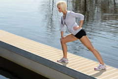 Sportfrauen-Ausdehnungskarosserie auf Wasserpier Stockfotografie