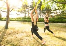 Sportfrauen, die Yoga draußen am Morgen tun Stockbilder
