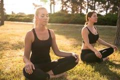 Sportfrauen, die Yoga draußen am Morgen tun Lizenzfreies Stockbild