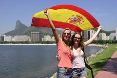Sportfreunde, die eine spanische Flagge in Rio de Janeiro .mer im Hintergrund halten. Lizenzfreie Stockfotos